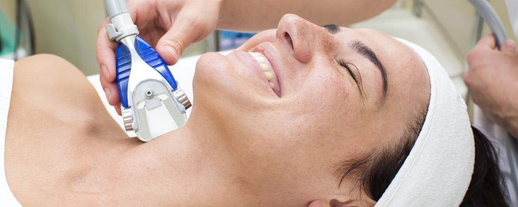 Woman smiling as Lymphatic Drainage Massage appartus massage her lymph nodes in neck